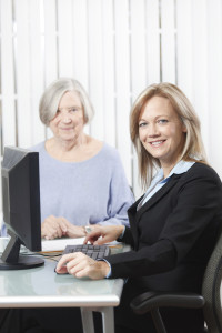 two woman working on a computer