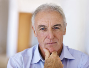 elderly man staring at the camera with his chin resting on his hand